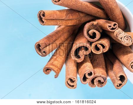 Ground cinnamon, cinnamon sticks on cerulean blue background. Flat lay or top view
