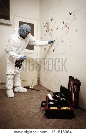 CSI technician collecting evidences of blood stains