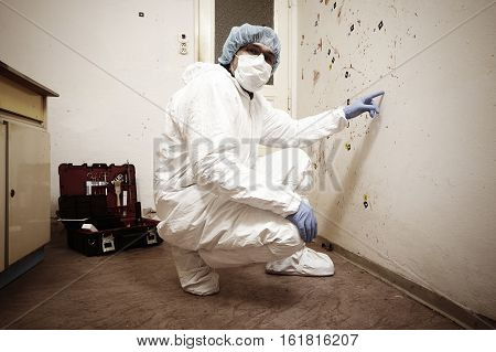 Criminologist technician collecting evidences of blood stains on crime scene