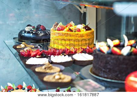 Cakes eclairs and cakes on display in the café. Showcases cafes restaurants. sweets desserts on display.