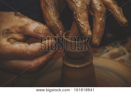 Master potter in his workshop produces pottery