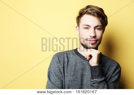 Portrait of a smart  young man standing against yellow background, studio shot