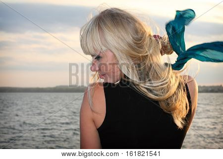 Blond young girl on background of the water surface and blue sky