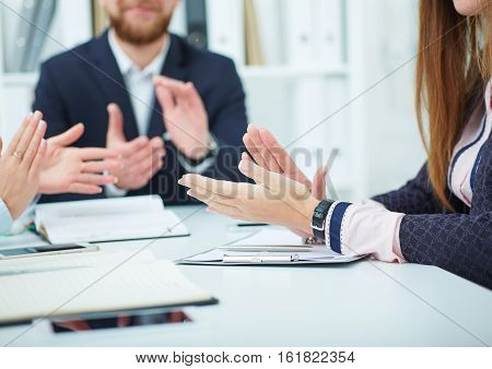 Cropped image of  business partners applauding at the meeting sitting in a row. Successful businesspeople applauding after presentation.