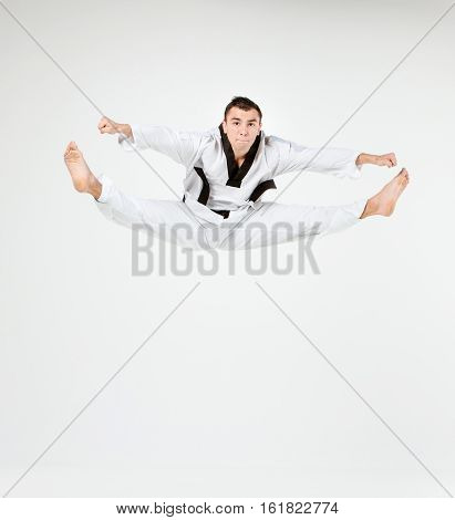 The karate man in white kimono and black belt training karate over gray background.