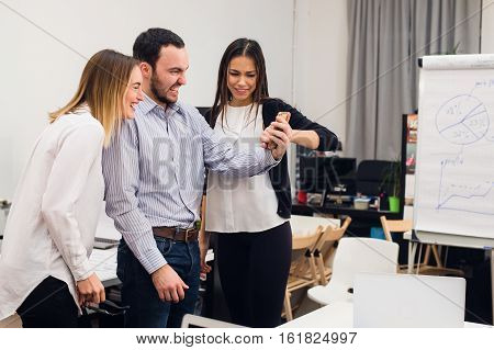 Group of four diverse cheerful co-workers taking self portrait and making funny gestures with hands at small office.