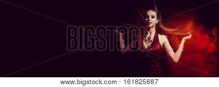 The girl in a red dress in fire flame