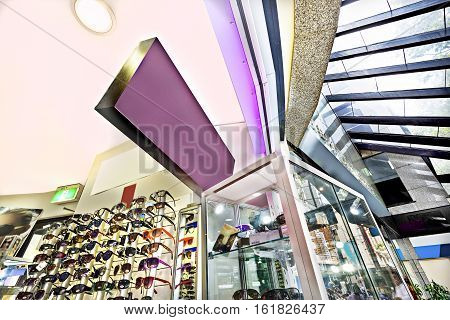 Glass show cases and sunglasses showed in a transparent cupboard in front of the shop beside sunglasses in a rack