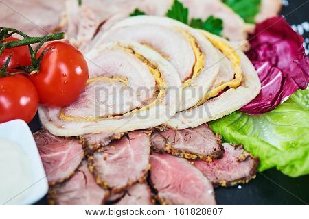Cold cuts of roast beef, baked ham, chicken roll and beef tongue served on a stone Board