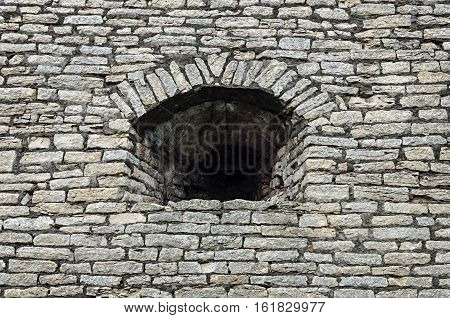 Old gray stone wall with embrasure in Krom (Kremlin) of Pskov Russia