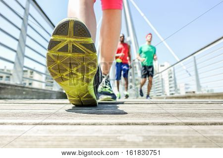 Close up of woman legs running with friends in urban wood city bridge - Young people doing jogging in sunny day - Healthy lifestyle concept - Focus on top left foot - Warm vivid filter
