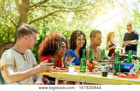 Happy friends toasting beer and having barbecue outdoor with back sun light - Young people having fun in bbq party - Friendshipsummerfun and dinner concept - Focus on left man eye - Warm filter