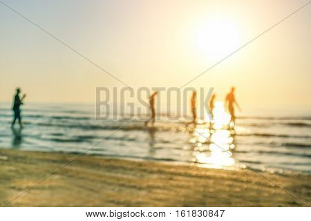 Blurred people walking throught the sea from sandy beach at sunrise - Defocused image - Blurry background - Vacation concept - Warm filter