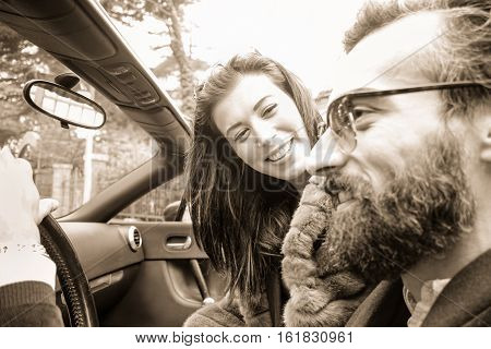 Hipster happy couple on road trip with convertible car - Fashion people having fun driving roadster cabriolet auto - Trendy concept - Black and white editing - Focus on woman - Warm sepia filter