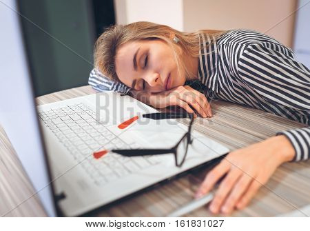 freelancer girl was tired and fell asleep at work at a desk near a white notebook.