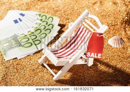 Deckchair on the beach discount label with the word sale and bank notes