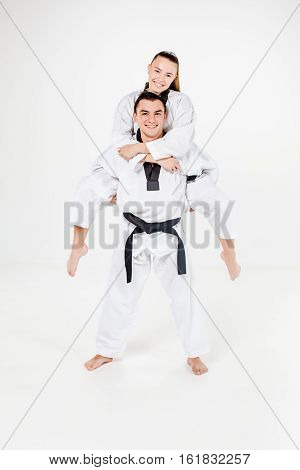 The karate girl and boy in white kimono and black belt posing over gray background.