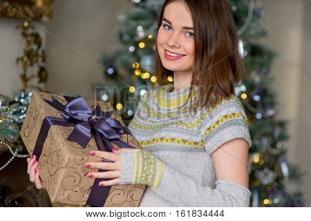 Portrait Of Attractive Girl In Pullover Holding Gift Box
