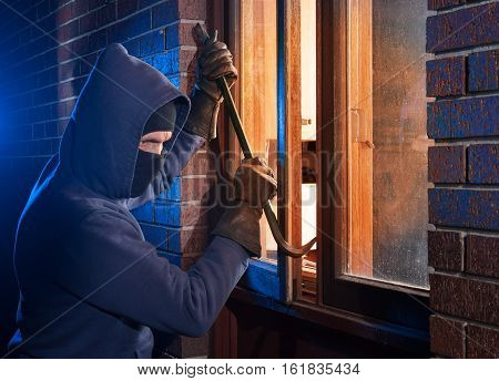 Hooded burglar breaking into a home with a crowbar