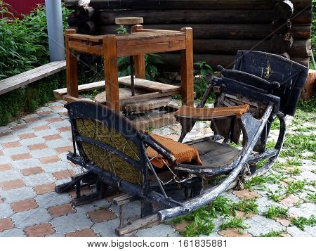 Old wooden sledge and  manual machine for sharpening knives in the village yard. Retro. Closeup. Ural, Russia.