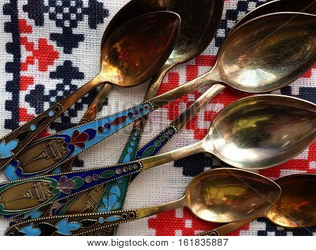 Tea and dessert spoons on a white linen tablecloths. The handle color enamel and a view of the tower. Retro. Closeup.