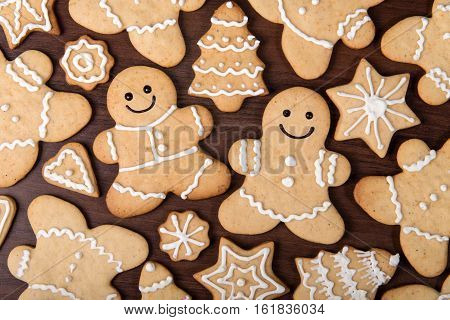 Christmas homemade gingerbread happy couple fir trees stars and hearts cookies over wooden background