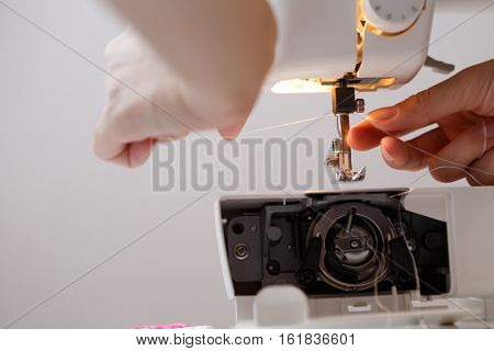 Girl inserts thread in sewing-machine