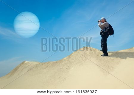 Brave tourist on a desolate planet taking photograph of its satellite