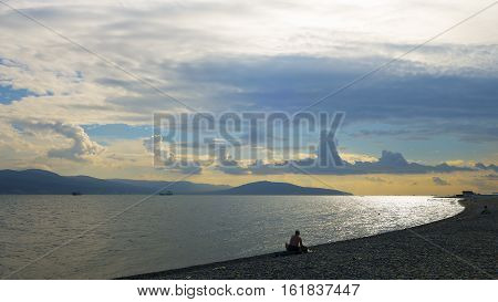Silhouette of fisherman at sunset by the calmwindless  sea. Seascape with beautiful sky and clouds of unexpected form