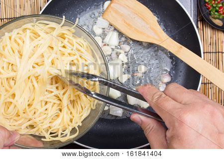 Chef putting Spaghetti for cooking with tongs / cooking spicy spaghetti concept