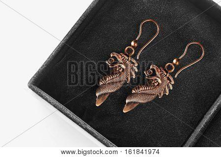 Bronze dragon earrings in black jewel box closeup