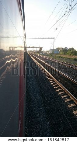 Train stops at the station. Railway track goes over the horizon.