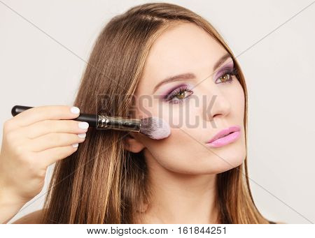 Woman Applying Rouge With Brush To Her Face