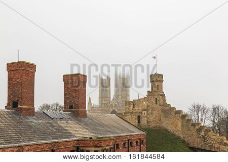 LINCOLN ENGLAND - DECEMBER 15: Lincoln Cathedral with Lincoln Castle wall and observatory tower in foreground. In Lincoln England. On 15th December 2016.