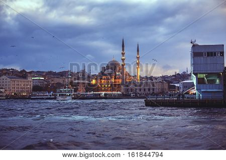 ISTANBUL - OCTOBER 2 2014: View on New Mosque Yeni Cami near Galata Bridge in evening time Istanbul Turkey