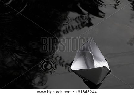 paper boat sailing on water surface, black and white