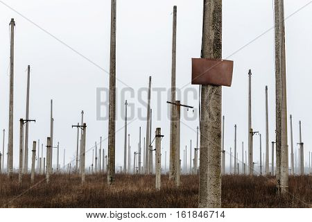 Many concrete pillars with the tablet for an inscription in a field near a disused power station.