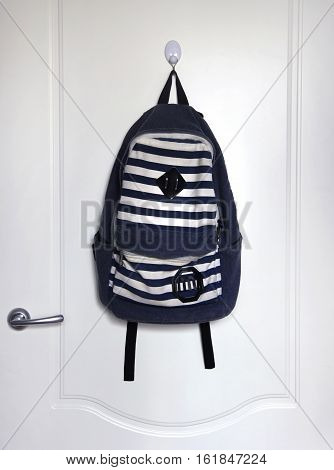 striped white and blue schoolbag hanging on white door