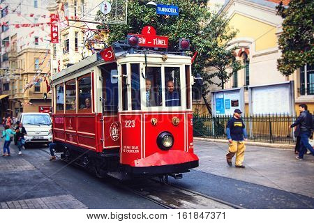 ISTANBULTURKEY - OCTOBER 6 2014: Old-fashioned red tram at the street Istiklal - the most popular destination in Istanbul. Nostalgic tram is the heritage tramway system. It was re-established in 1990 and gained much popularity.