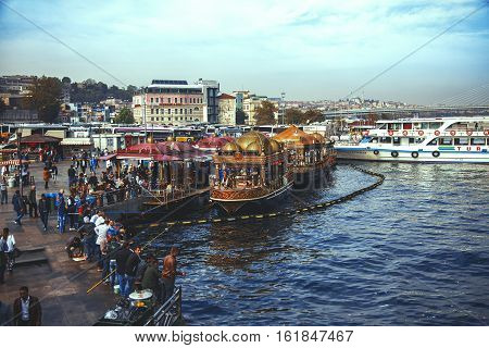 ISTANBUL TURKEY - OCTOBER 7 2014: Embankment of Eminonu from Galata bridge and fisher boats