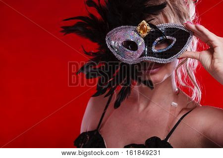 Party fashion people concept. Attractive woman wearing carnival mask. Beautiful mature lady wearing black elegant dress.