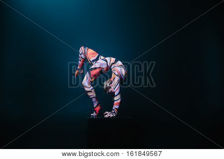 Young Flexible Blonde Circus Acrobat Posing In Studio In Costume. Doing Equilibre Balance Handstand