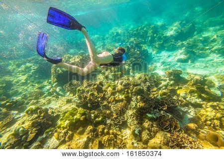 Female apnea swims in tropical turquoise sea of Racha Noi, Phuket in Thailand.
