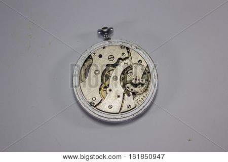 old clock with no back cover, clockwork on a white background
