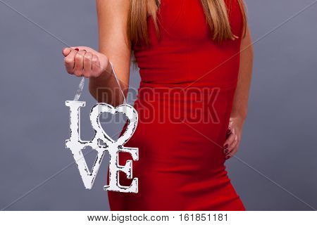 Valentines Day. Woman wearing red dress holding sign love symbol on grey background