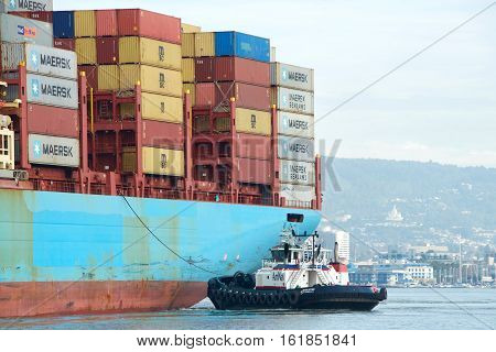 Oakland CA - December 13 2016: Tugboat REVOLUTION assisting cargo ship GERD MAERSK maneuver into the Port of Oakland the fifth busiest port in the United States.