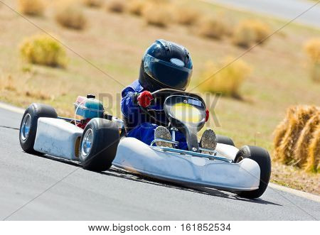 Young Kid Racing A Go Cart Around A Track.