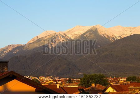 Morning sunrise view in glowing light of the Pirin Mountain and rooftops of the town of Bansko in summer a popular Bulgarian ski resort and tourist destination