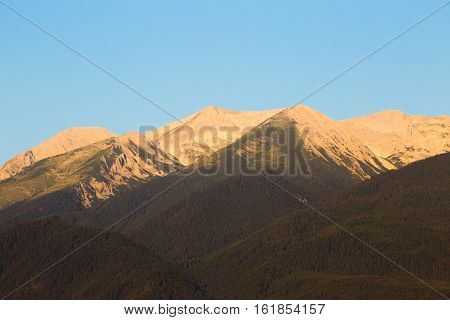 Morning sunrise view in glowing light of the Pirin Mountain and Vihren Kutelo and Banski suhodol peaks from Bansko in summer a popular Bulgarian ski resort and tourist destination.