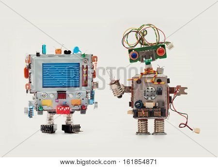 Robots in love. Funny man mechanism with monitor head, love heart abstract message on blue screen Woman robot green circuit face, electrical wire hairstyle, color blue red eyes, light bulb in hand